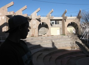 CG surveys the amphitheater, with its perpetually empty storefronts (background circles).